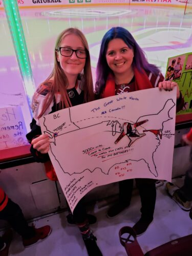 My daughter, Bri, and I at the Washington Capitals hockey game holding a sign we made and brought with us!